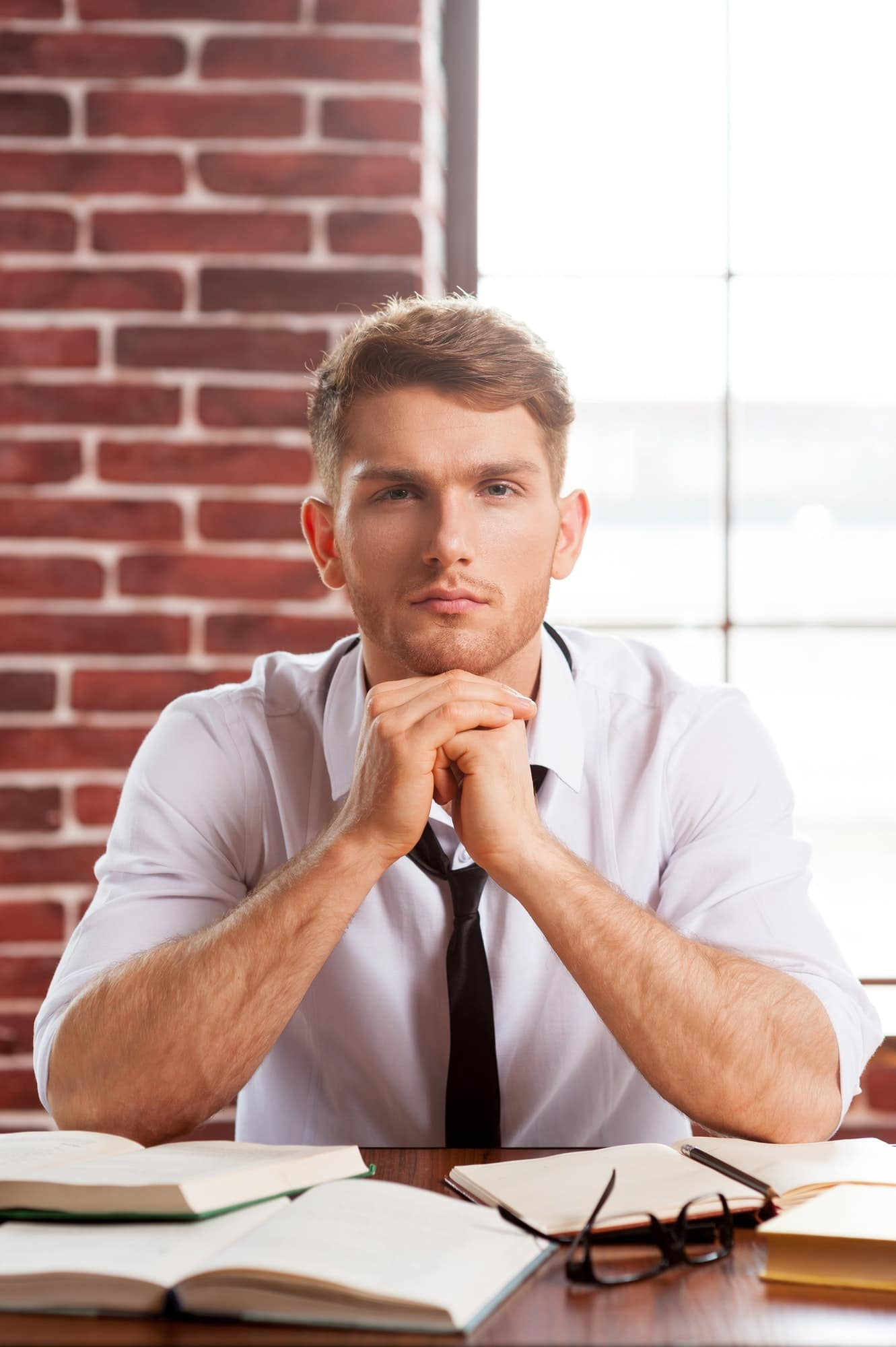 Only creative thinking. Thoughtful young man in shirt and tie holding hands clasped and looking at
